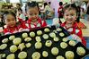 2021年9月17日,江西省德兴市城南幼儿园小朋友,开心将自己亲手制作的童趣月饼准备送去烤制。卓忠伟/视觉中国